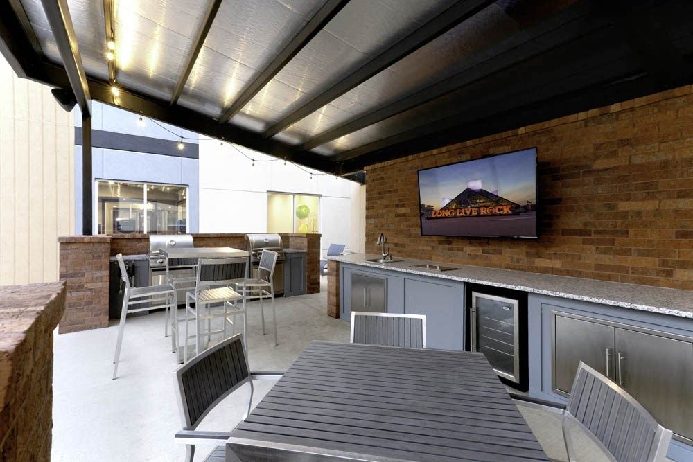 Outdoor community space with grills, refrigerator and kitchen space