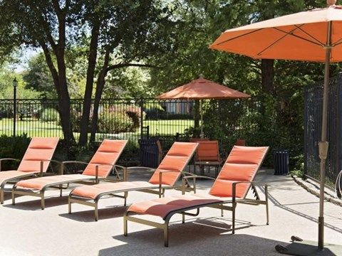 orange outdoor lounge chairs next to pool