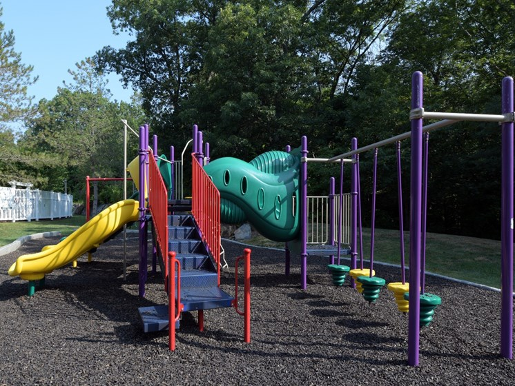 Large playground area with slides and swing sets at Cumberland Crossing, Cumberland, RI, 02864