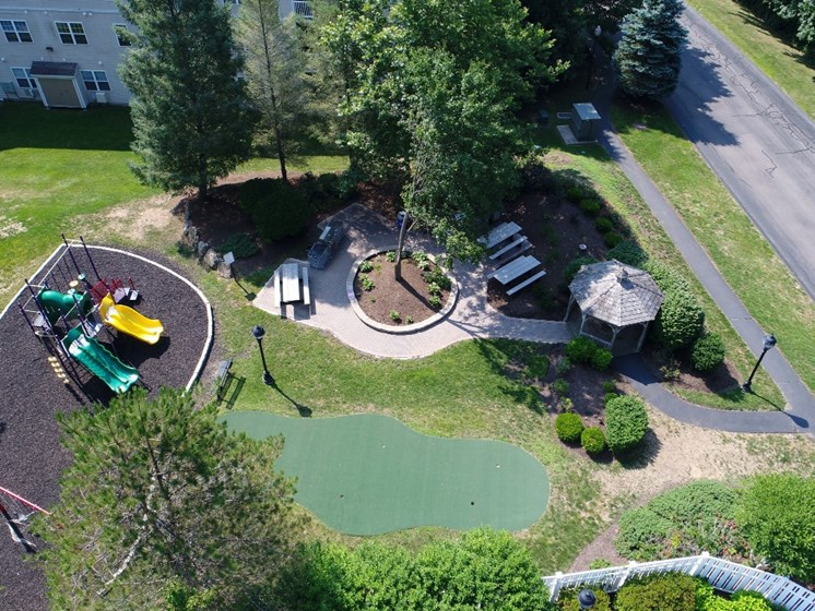 Aerial view of outdoor community amenities including playground, gazebo, and picnic and grilling areas at Cumberland Crossing, Rhode Island, 02864