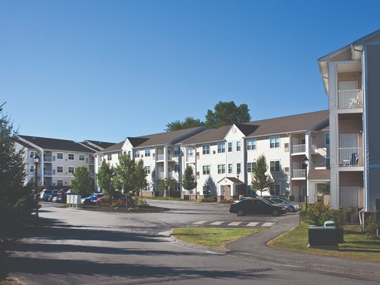 Exterior shot of on-site parking and apartment buildings at Liberty Commons, Maine