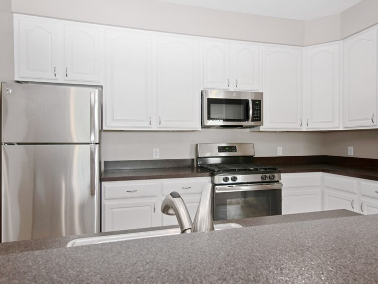 Granite Counter Tops and White Cabinets in Fully-Equipped Kitchens at Liberty Commons, South Portland, ME