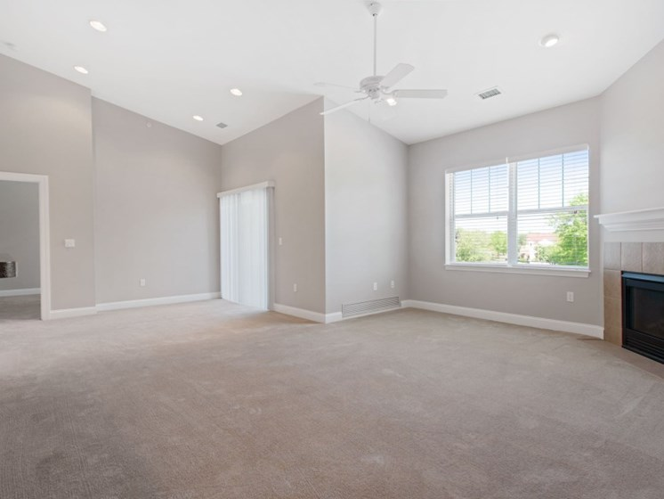 Spacious, brightly lit living room with fireplaces, ceiling fan, and access to private balcony at Liberty Commons, Maine