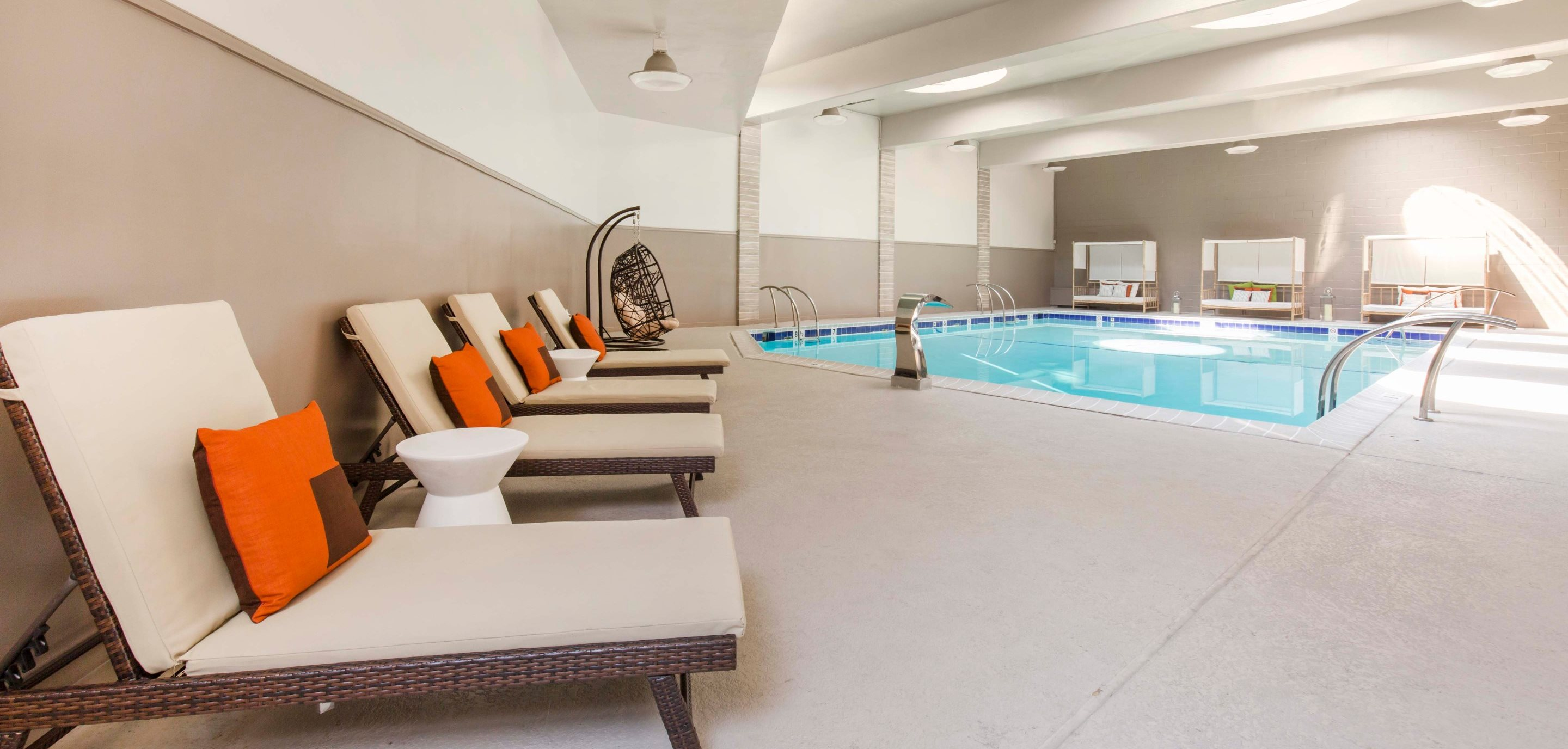 Indoor swimming area with tan and brown lounge chairs, orange accent pillows, and natural sunlight coming through the ceiling