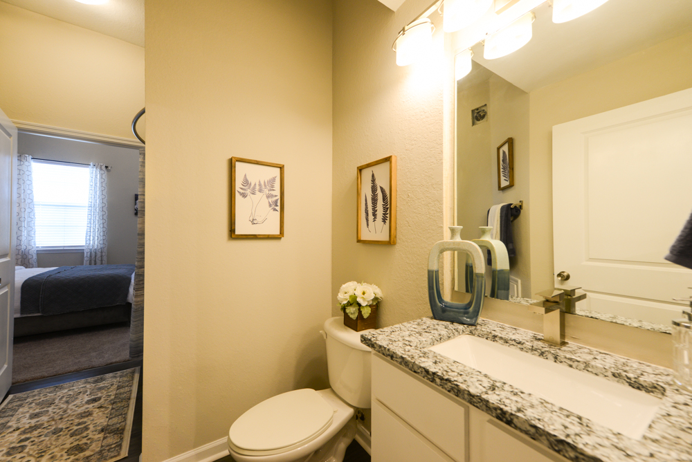 Toilet and kitchen sink with large mirror at Century Deerwood Park