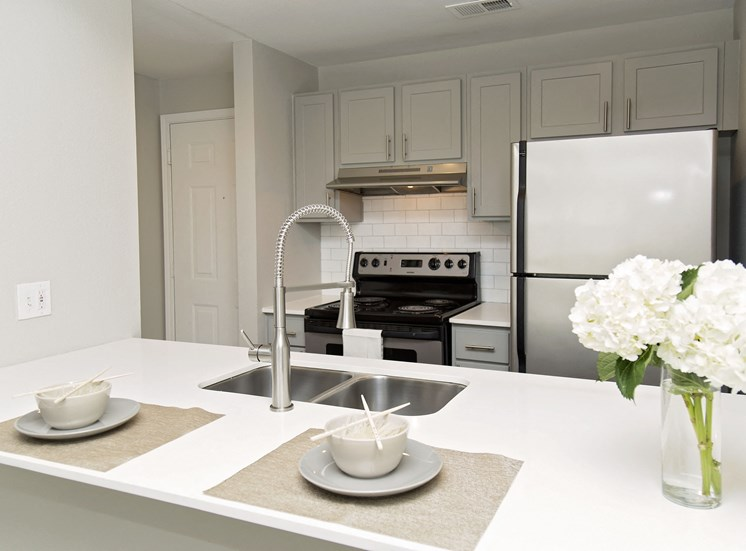 Model kitchen with place settings and floral arrangement on counter