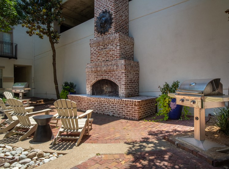 Outdoor chairs in front of BBQ and brick fireplace