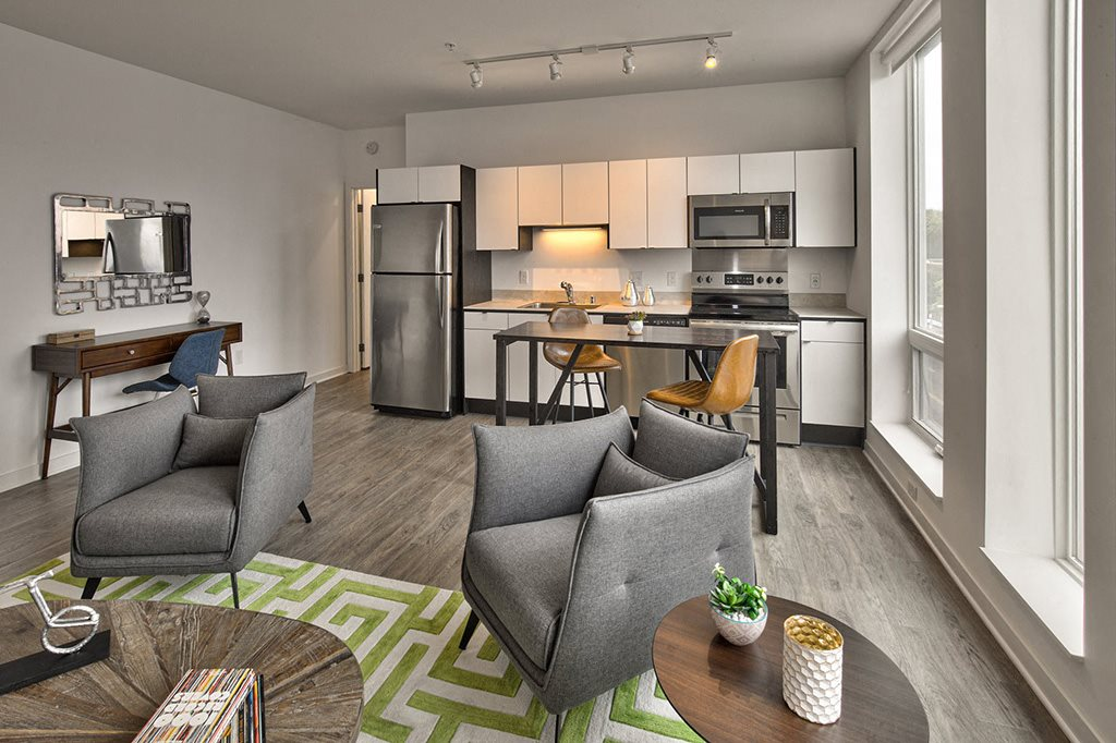 Living room and kitchen with island table and stainless steel appliances