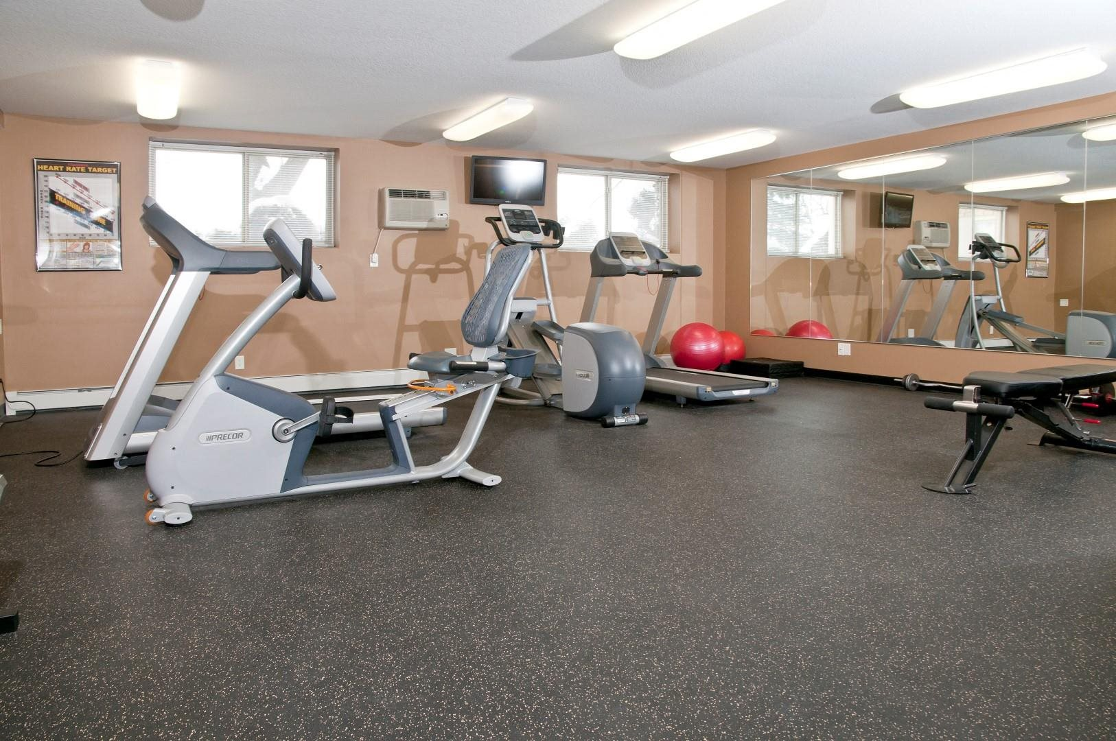 Bass Lake Crossing Fitness Center With Floor To Ceiling Mirrors on Full Wall and Aerobic Equipment
