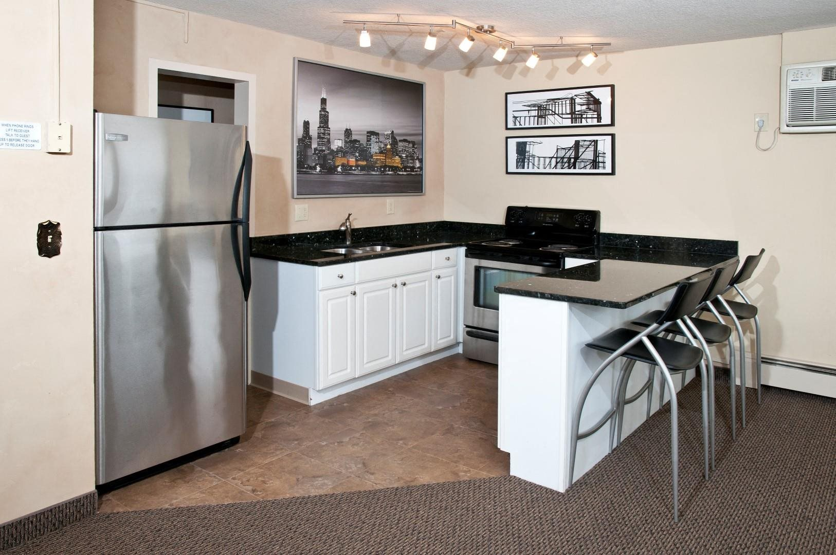 Boulevard 100 Apartments Kitchen with White Cabinetry, Black Counter Tops and Stainless Steal Appliances
