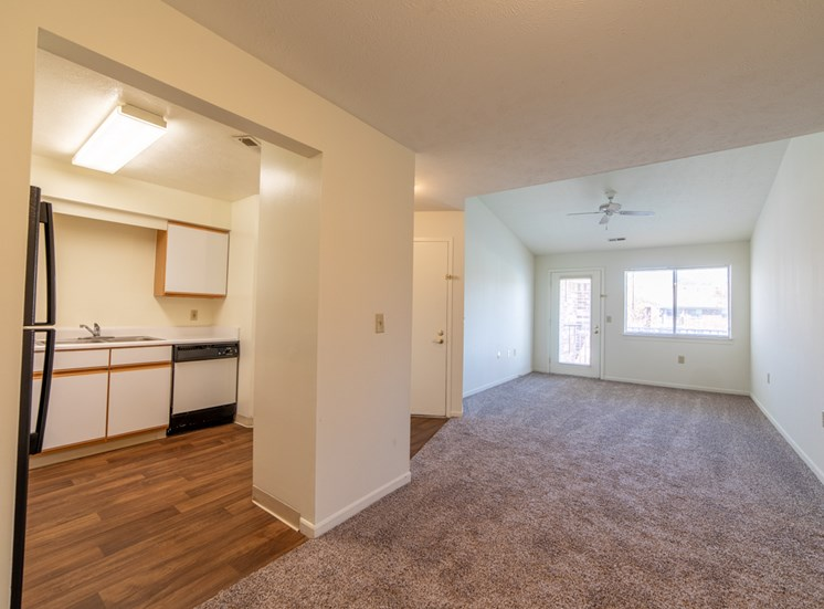 living room with carpet and view into kitchen