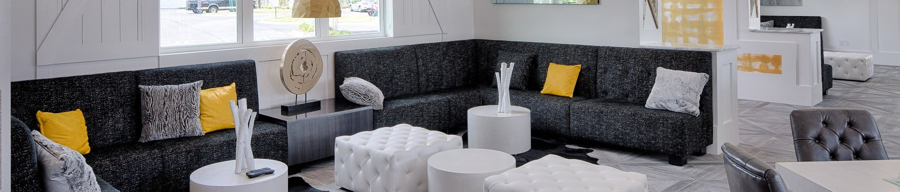 Leasing office in large couch, chairs, ottomans, tables and gray, yellow and white pillows