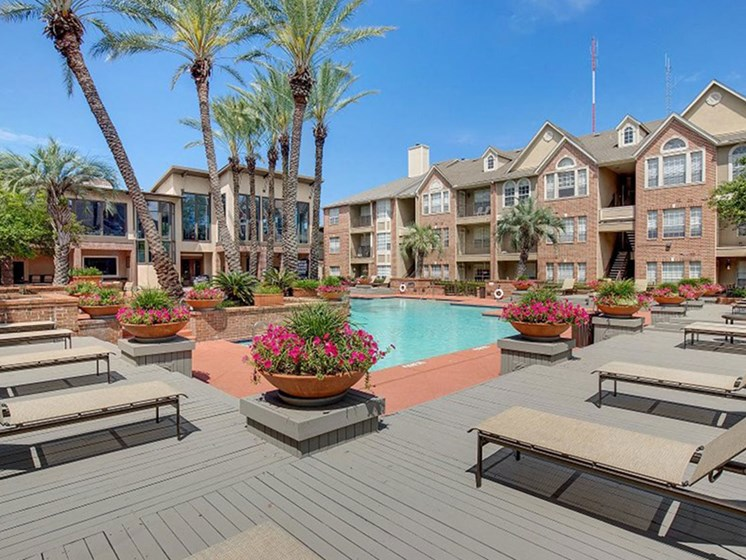Pool Deck With Lounge Chairs at The Village at Bellaire Apartments in Houston, Texas