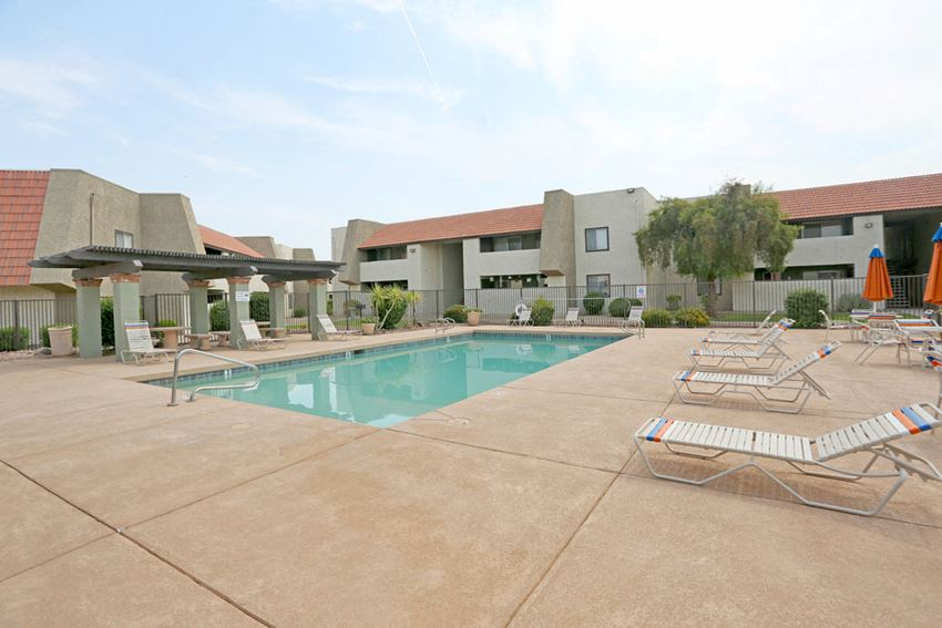 Pool deck with lounge chairs and apartment buildings in the background.