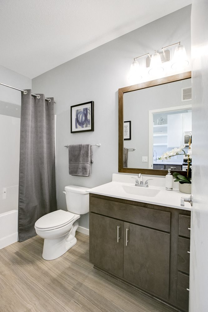 Quartz bathroom countertops with hardwood-style flooring at The Central apartments near downtown Minneapolis MN 55408