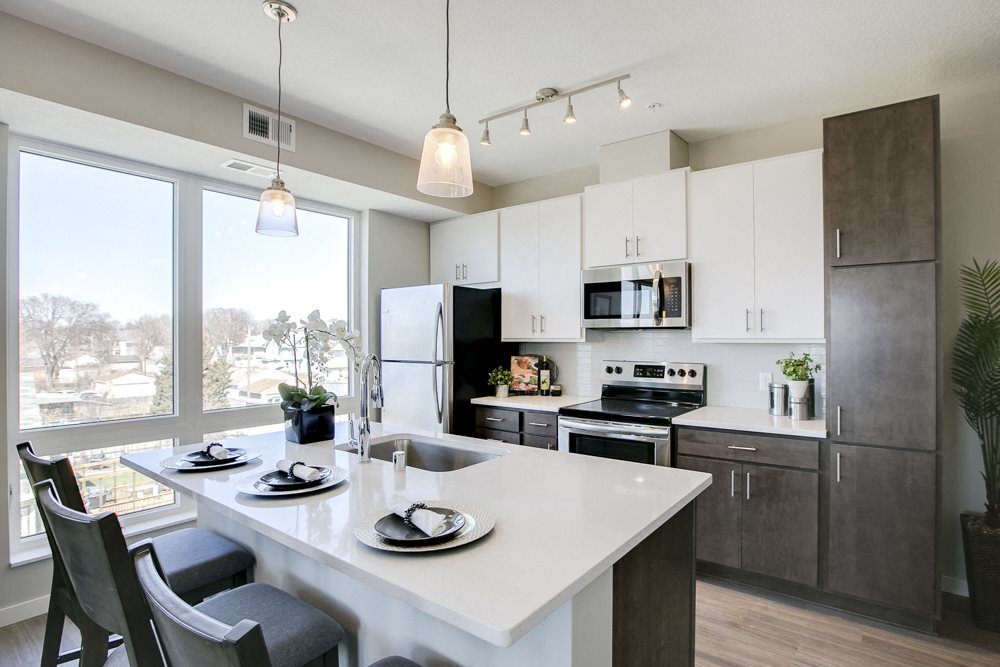 View of kitchen with white and dark contemporary cabinets and quartz countertops at The Central apartments near downtown Minneapolis MN 55408