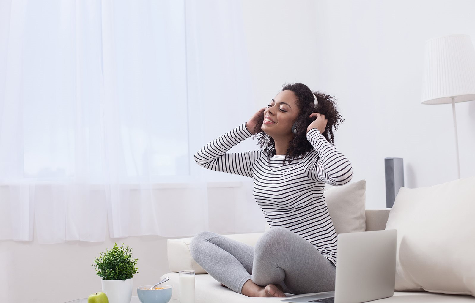 Girl listening to music on the couch | Stockton, CA 95207 | Abbey Pointe Apartments