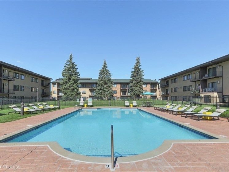 Outdoor sun sparkling pool with plenty of seating at Equinox Apartments