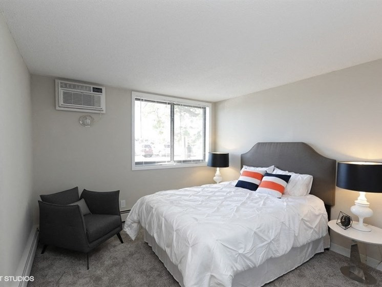 Large bedroom with plush carpeting at Equinox Apartments