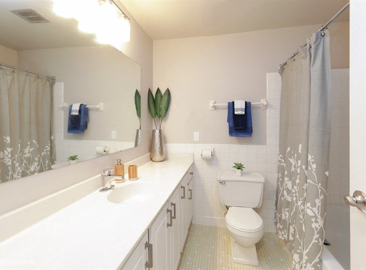 Large bathroom with tile flooring at Equinox Apartments