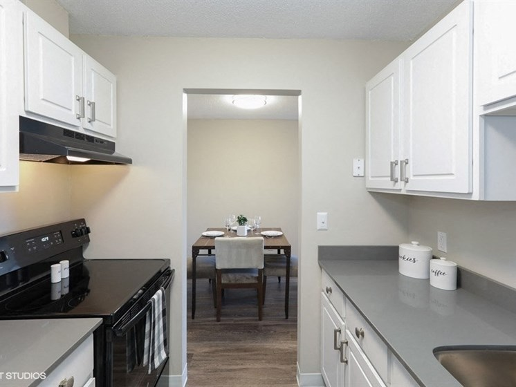 Kitchen with rich white wood cabinetry and tons of counter top space at Equinox Apartments
