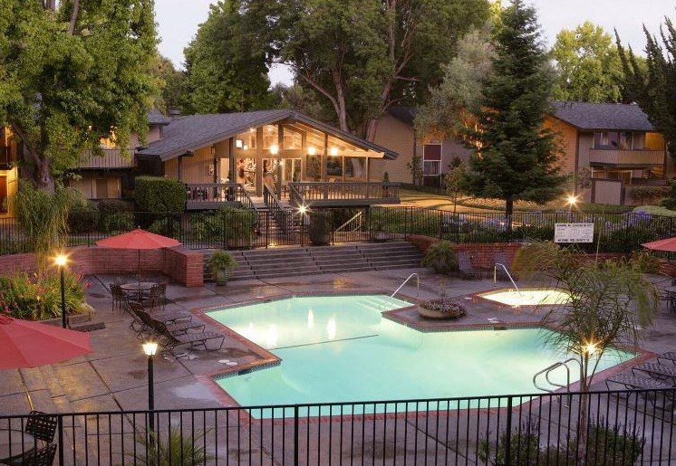 Night view of landscaping, community pool and hot tub