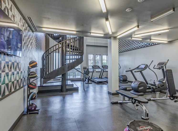 Two-story 24/7 fitness center featuring Technogym® cardio equipment with iPod connectivity, viewing screens for internet