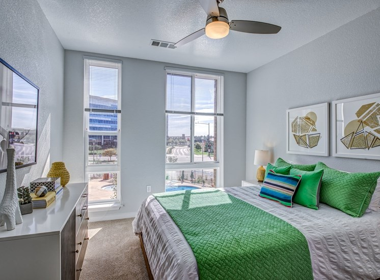 bedroom with 2 large windows and ceiling fan
