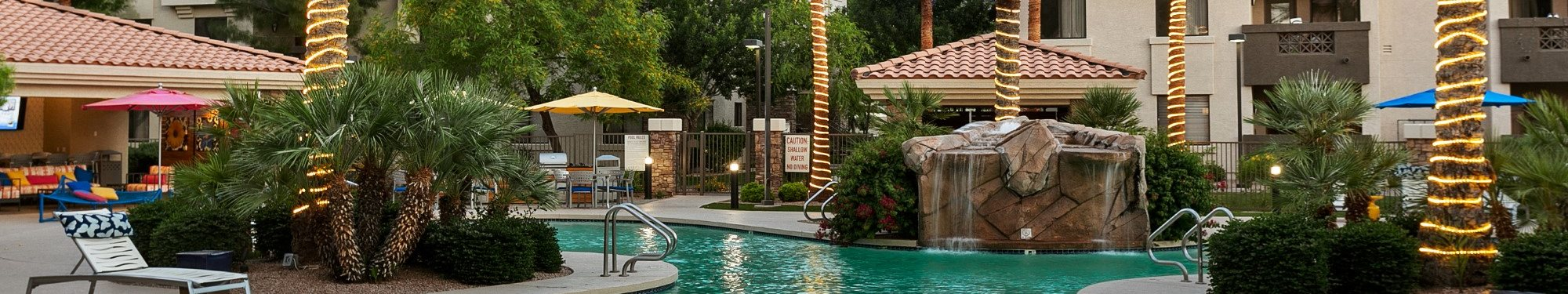 San Portella Apartments Pool Area Waterfall Banner