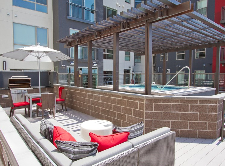 Rooftop lounge with pool, gas grill, shaded picnic seating, lounge chairs, with apartment exterior in the background