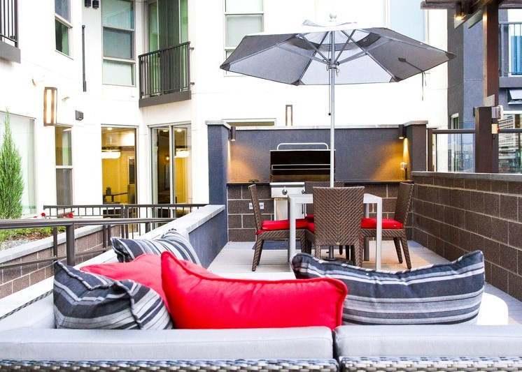 Rooftop patio with gas grill, table with four chairs and umbrella, lounger couch with red and gray pillow and the building exteriors in the backhground