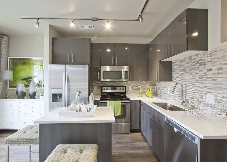 Kitchen with hardwood style flooring, white cabinets, granite style countertops, tiled backsplash, stainless appliances, track lighting and bar stools