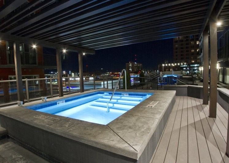 Rooftop swimming pool at night with pool lights on under gazebo