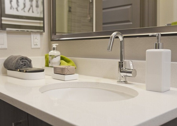Close up with bathroom sink with brush nickel faucet, white countertops, and modern bathroom decor