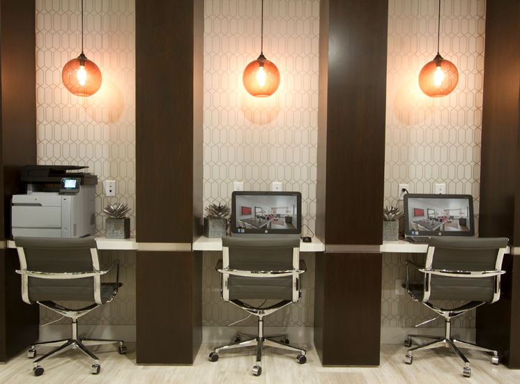 Resident business center with computers, chairs, and pendant lighting