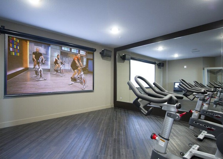 Fitness center with stationary bikes, mirrored wall and large tv for workout videos