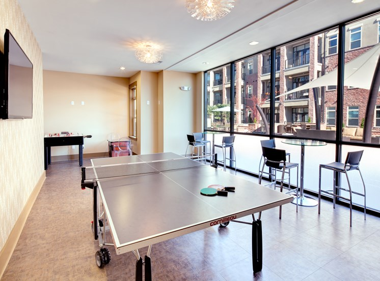Resident clubhouse with  TV and ping pong table at St. Mary's Square Apartments, NC, 27605