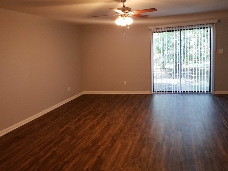 hardwood inspired flooring and ceiling fan in living room at Heritage Park Apartments in Tallahassee, FL 32304