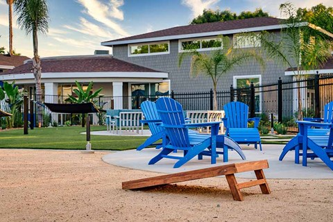 Cornhole by lounge chairs Exterior building with grass |Nola624 Apts in West Covina