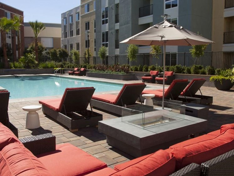 Outdoor lounge seating with fire pit in pool area