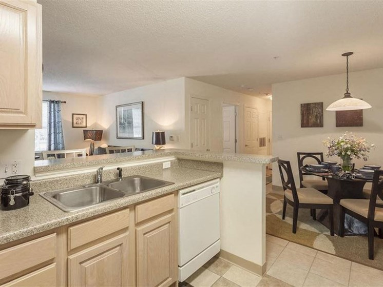 Kitchen Counter With Sink Near Dining Room at Quail Run Apartments in Stoughton, MA