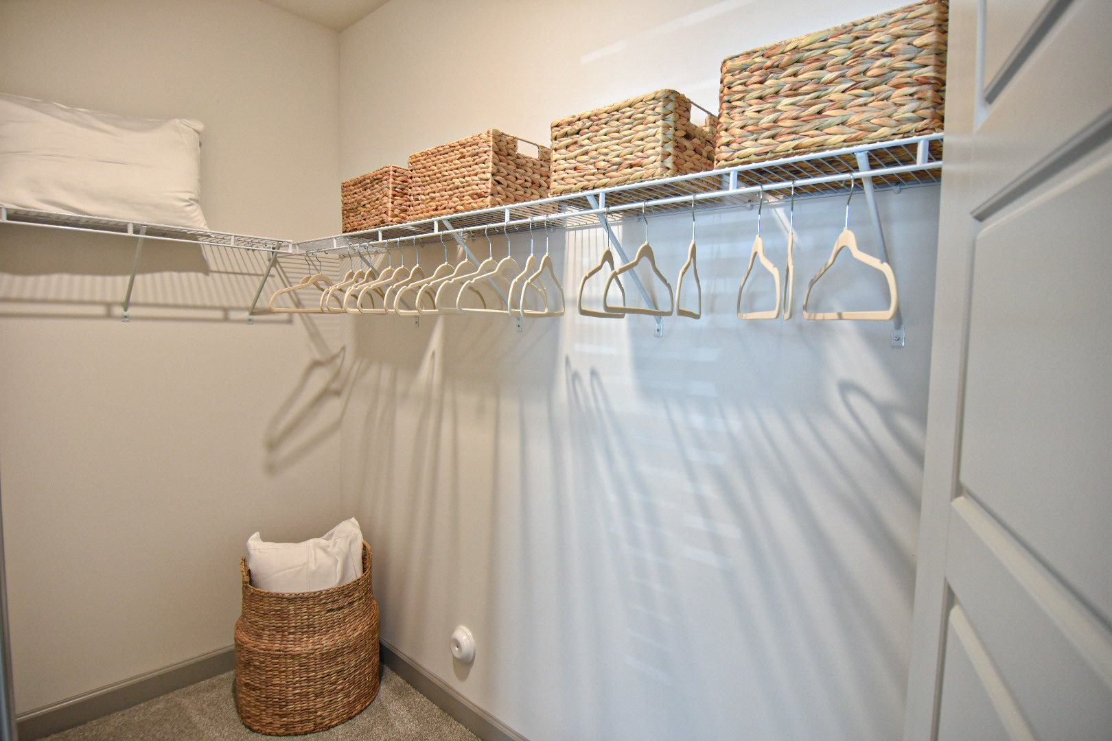 Walk in closet with wicker baskets and felt hangers Hawthorne at Smith Creek