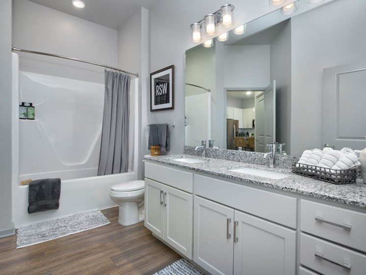 Relax after a long day in your bathroom with soaking tub, new cabinets, wood plank flooring at The Edison Apartments in Fort Myers, FL 33905