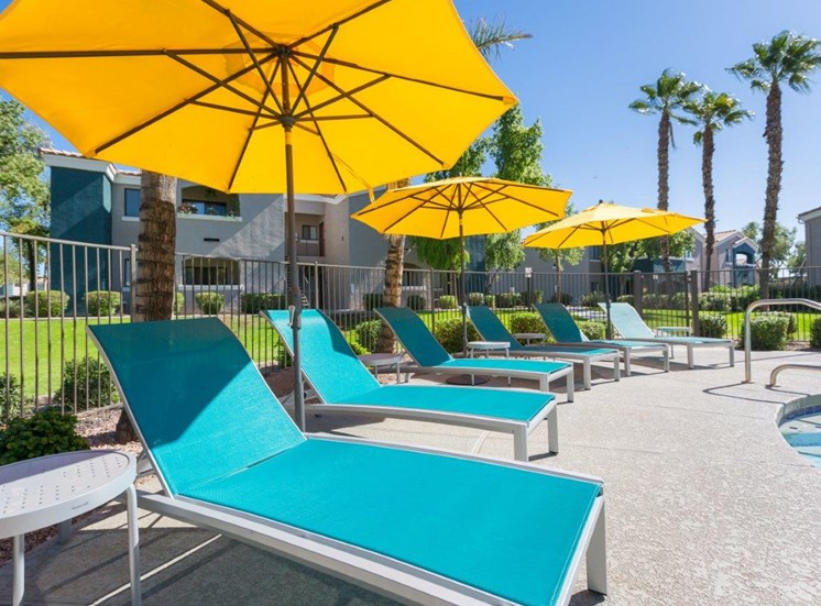 Lounge chairs with umbrellas by pool