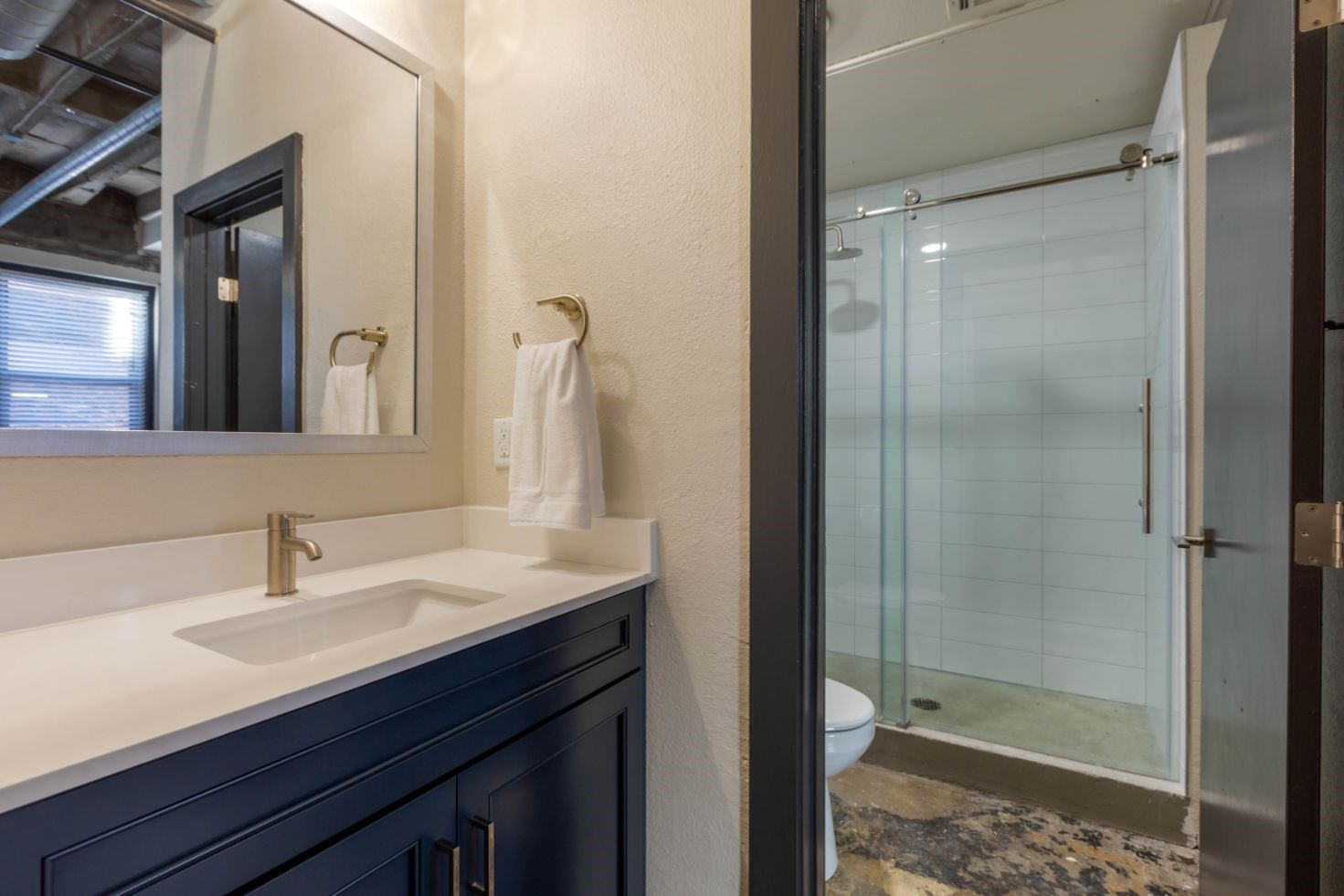 The Indi at Uptown Square Apartments |Bathroom with Glass Enclosed Shower