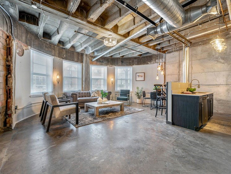 open concept industrial style loft with model living room furnishes and kitchen island nearby