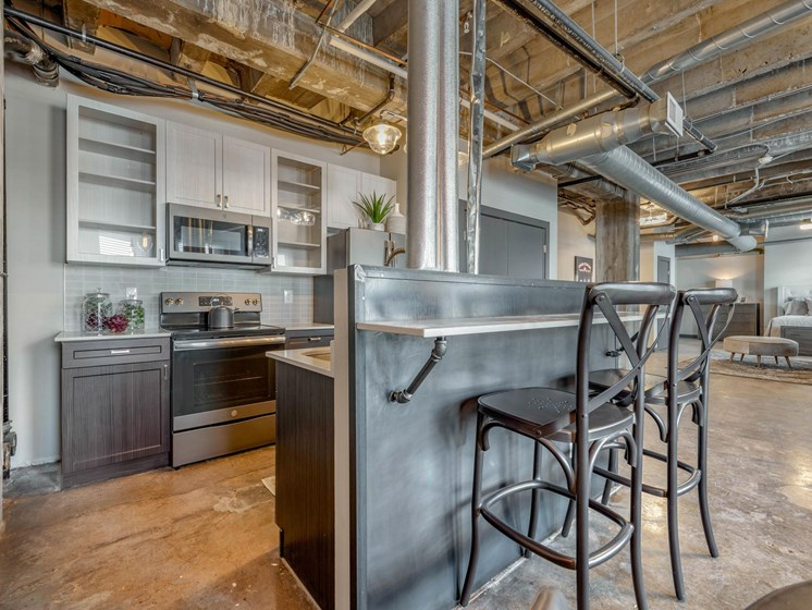 industrial style loft kitchen with glass door cabinetry, stainless appliances, and kitchen island