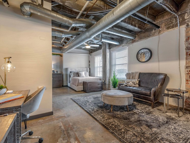 industrial style, open concept loft with model furnishes demonstrating sitting area, desk, and bedroom furnishings