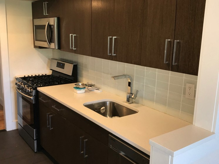 Stainless steel appliances, dark wood cabinets and granite counters