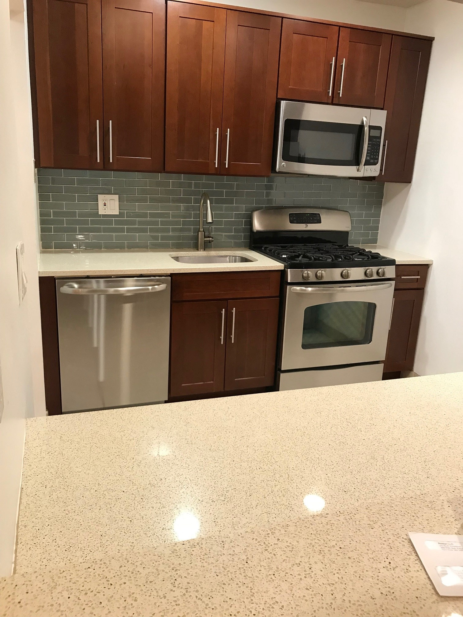 Renovated pass through kitchen with stainless steel appliances, dark wood cabinets and granite counters